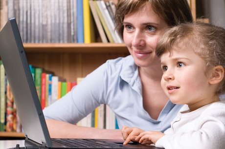 Girl with carer playing on a laptop