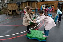 Children in winter coats playing in school playground
