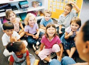 happy children listening to teacher reading story