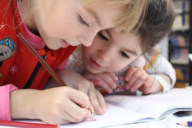 Two young girls drawing in a notebook