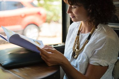 Woman sitting by a window and reading some training notes