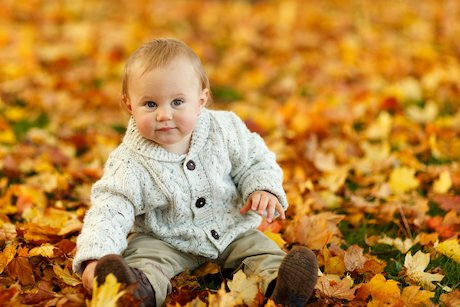 baby playing with leaves outside