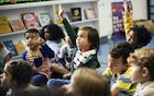 children raising hands in classroom discussion