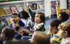 children raising hands in classroom discussion
